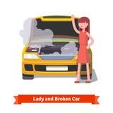 看在她残破的汽车下敞篷的妇女  免版税库存图片