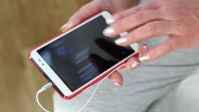 看在她的智能手机的妇女照片 拿着一个白细胞电话的妇女 影视素材