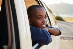 看在家庭旅行的车窗外面的男孩 免版税库存照片
