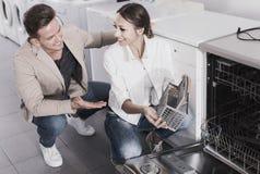 看在家用电器的夫妇洗碗机购物 免版税库存图片