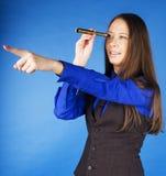 看在小望远镜和指向在蓝色背景,生活方式旅行人概念的年轻俏丽的深色的女孩 免版税图库摄影