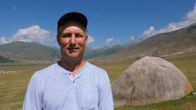 看在山风景和绿色高地的照相机的盖帽的画象人 股票录像