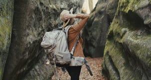 看在岩石附近的帽子的旅客女孩 库存图片