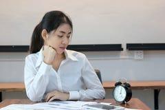 看在工作场所的可爱的年轻亚裔女商人一个时钟在办公室 免版税库存照片