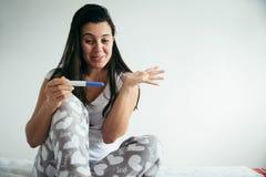 看在幸福的少妇pregnance测试 免版税库存照片