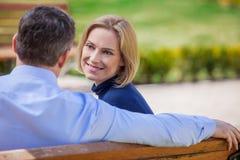 看在彼此的成人微笑的夫妇坐长凳 免版税库存照片