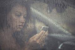 看在手机和在窗口里的哀伤的妇女读消息与在汽车的雨下落 免版税库存图片