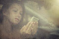看在手机和在窗口里的哀伤的妇女读消息与在汽车的雨下落 免版税图库摄影