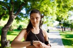 看在手表的年轻健身女孩的图片 背景蓝色云彩调遣草绿色本质天空空白小束 图库摄影