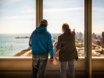 看在摩天大楼窗口外面的两个访客密执安湖 免版税库存图片
