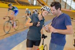 看在教练的秒表的骑自行车者时间 免版税图库摄影