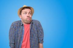 看在旁边与怀疑的夏天帽子的年轻人 免版税库存照片