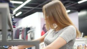 看在时兴的精品店的衣裳的时髦的女孩 4K 股票录像