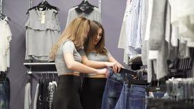 看在时兴的精品店4K的长裤的两个俏丽的女孩 股票视频
