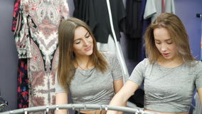 看在时兴的精品店4K的长裤的两个俏丽的女孩 影视素材