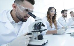 看在显微镜的男性化验员样品 图库摄影