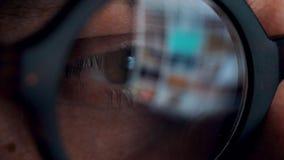 看在显示器和冲浪的互联网的玻璃的人 显示器屏幕在玻璃被反射 股票录像