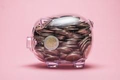 看在有金钱硬币的存钱罐里面 免版税库存图片