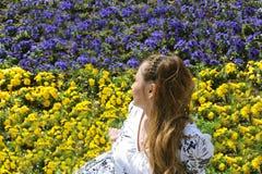 看在有黄色和蓝色花的草甸的妇女 库存照片