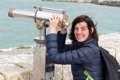 看在望远镜双筒望远镜海边海洋海滩的中间年迈的美女在旅游业假期时 库存图片
