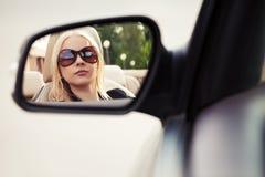 看在汽车后视镜的白肤金发的妇女 免版税库存图片