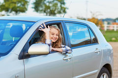 看在汽车外面的美丽的年轻司机把握关键 免版税库存照片