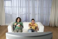 看在沙发的愉快的人电视  免版税库存照片