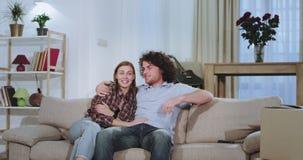 看在沙发的美好的夫妇电视在他们的新房在一坚硬移动的天以后他们享受时间微笑 股票录像