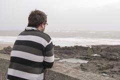 看在海的年轻人在一个大风天 图库摄影