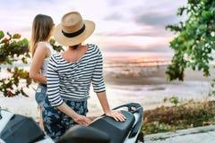 看在海的日落的两girlfreinds旅客在他们的motojorney期间 库存照片