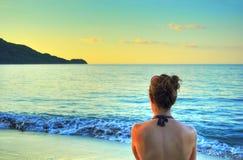 看在海滩的妇女日落 免版税图库摄影