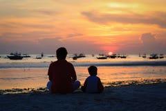 看在海滩的父亲和儿子日落 免版税库存照片