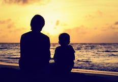 看在海滩的父亲和小儿子日落 免版税库存图片