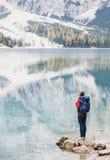 看在湖的阿尔卑斯山的年轻女人旅客 旅行、冬天和活跃生活方式概念 免版税库存图片