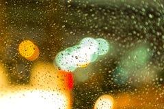 看在湿城市通过挡风玻璃从汽车里边雨 免版税库存图片