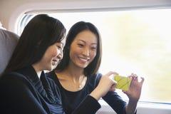 看在火车的两名妇女手机 免版税图库摄影
