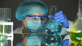 看在烧瓶,水质分析的防护制服的科学家蓝色液体 影视素材