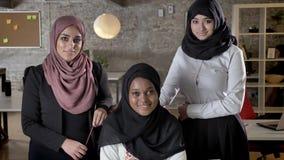 看在照相机和微笑在现代办公室,有同事的黑人回教妇女的hijab的三名年轻回教妇女的在 影视素材