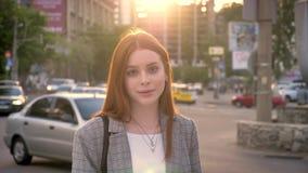 看在照相机和身分的年轻姜妇女画象在城市街道上在日落期间,微笑,汽车交通  影视素材
