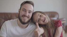 看在照相机微笑的英俊的有胡子的人和逗人喜爱的正面女孩画象  孩子倾斜她的头对 股票视频