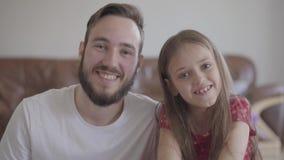 看在照相机微笑的英俊的有胡子的人和逗人喜爱的正面女孩 孩子倾斜她的头给人 影视素材
