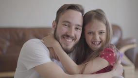 看在照相机的英俊的有胡子的人和逗人喜爱的正面女孩微笑,拥抱人的孩子 o 股票视频