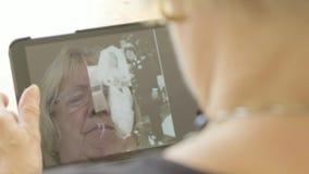 看在片剂计算机上的一名资深妇女的反射老照片 影视素材