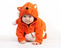 看在白色的狐狸服装的男婴照相机 免版税库存照片
