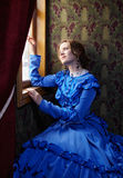 看在突然行动的蓝色葡萄酒礼服的少妇窗口 库存图片