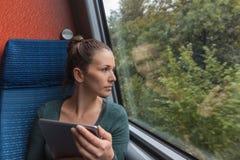 看在窗口外面和使用片剂的年轻女人为学习,当旅行乘火车时 免版税图库摄影