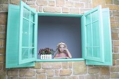看在窗口外面的女孩 免版税图库摄影