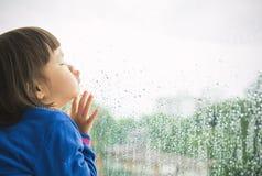 看在窗口外面的小女孩 免版税库存图片