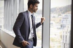 看在窗口外面的年轻商人在办公室 免版税图库摄影