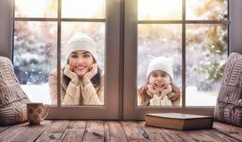 看在窗口的孩子和妈妈,站立户外 免版税库存照片